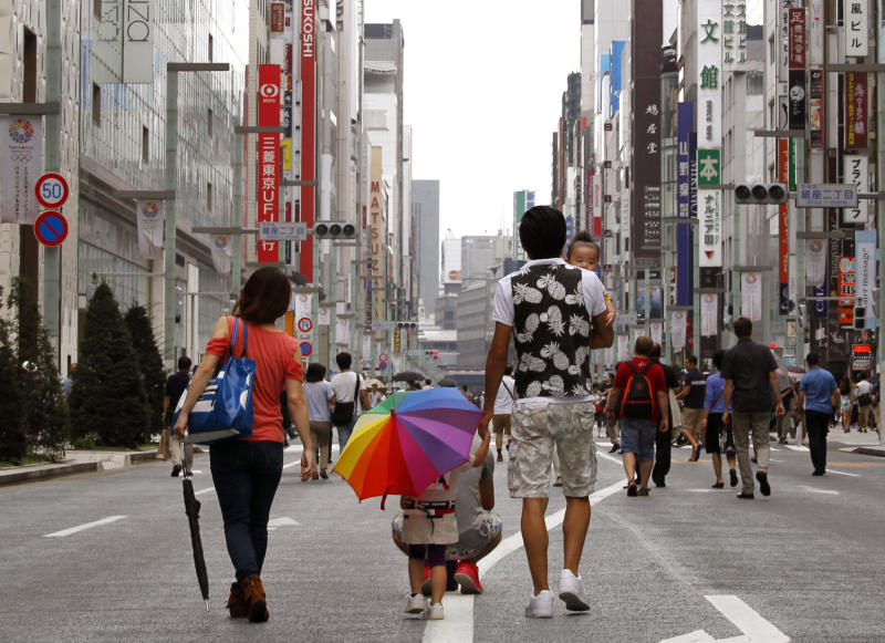 In this Sept. 8, 2013 photo, passersby walk on a Ginza street closed off to traffic on Sundays, in Tokyo. Japan's economy expanded faster in April-June than earlier reported, according to a revised estimate showing a real annualized growth rate of 3.8 percent, thanks to higher spending on private and public investment. The Cabinet Office also said Monday that the economy expanded 0.9 percent from the previous quarter, compared with an earlier estimate of a 0.6 percent increase. (AP Photo/Shuji Kajiyama)