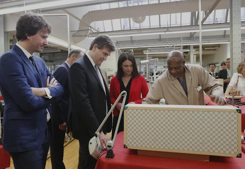 """French Minister for Industrial Recovery Arnaud Montebourg, 2nd left, with Trade and Tourism deputy Minister Sylvia Pinel reacts with LVMH workers during a visit of """"Particular operation days"""" in LVMH, the world's largest luxury company at the factory of Vuitton, in Asnieres north of Paris Saturday June 15, 2013. At left, LVMH member of the board of directors Antoine Arnault looks one. (AP Photo/Jacques Brinon)"""