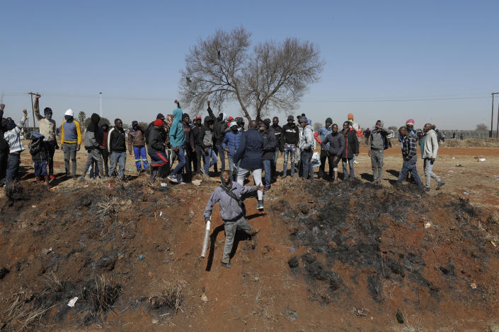 A community member, center, facing the crowd, speaks to a group of men in an effort to stop them from entering a shopping mall in Vosloorus, east of Johannesburg, South Africa, Wednesday July 14, 2021. South Africa's rioting continued Wednesday as police and the military struggle to quell the violence in Gauteng and KwaZulu-Natal provinces. The violence started in various parts of KwaZulu-Natal last week when Zuma began serving a 15-month sentence for contempt of court. (AP Photo/Themba Hadebe)