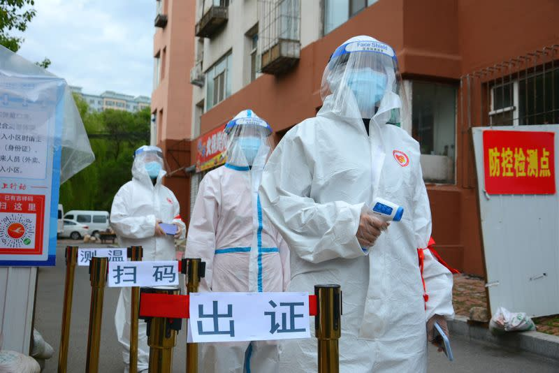 Volunteers in protective suits are seen a checkpoint following the coronavirus disease (COVID-19) outbreak, in Jilin