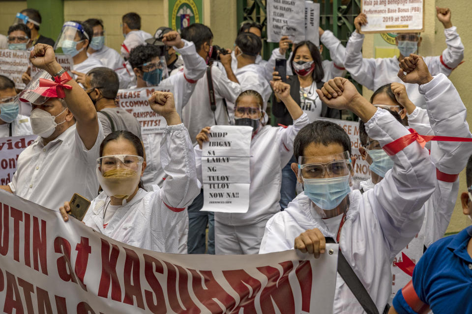 FILE PHOTO: Health workers wearing hazmat suits raise their fists as they protest their unreleased benefits amid the pandemic, outside the Department of Health headquarters on September 1, 2021 in Manila, Philippines. (Photo: Ezra Acayan/Getty Images)