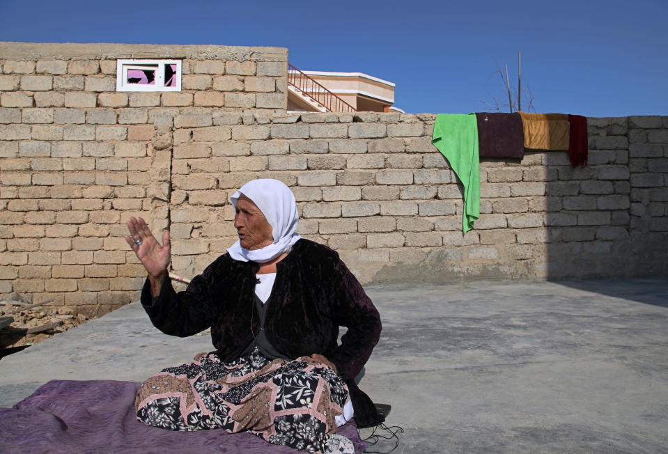 A Yazidi woman Farso Mato Sabo, 89, a survivor of Islamic State atrocities recounts her harrowing tale in the village of Tal Binat, Sinjar, Iraq. Friday Dec. 4, 2020. A new agreement aims to bring order to Iraq's northern region of Sinjar, home to the Yazidi religious minority brutalized by the Islamic State group. Since IS's fall, a tangled web of militia forces have run the area, near the Syrian border. Now their flags are coming down, and the Iraqi military has deployed in Sinjar for the first time in nearly 20 years. (AP Photo/Samya Kullab)
