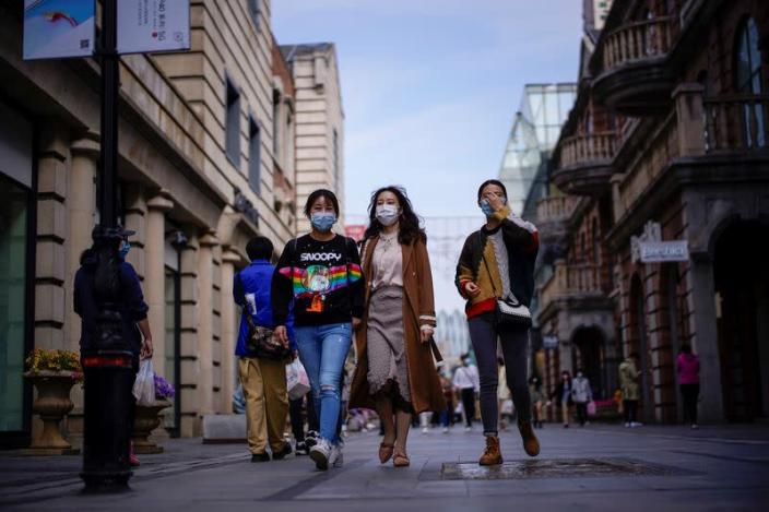FILE PHOTO: People wearing face masks are seen at a main shopping area after the lockdown was lifted in Wuhan