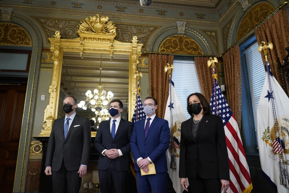 Pete Buttigieg, second left, after being sworn in as Transportation Secretary by Vice President Kamala Harris, right, in the Old Executive Office Building in the White House complex in Washington, Wednesday, Feb. 3, 2021, with Chasten Buttigieg, second right and Doug Emhoff, left. (AP Photo/Andrew Harnik)