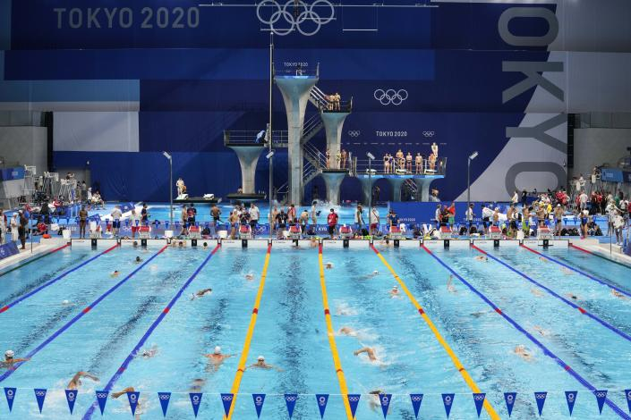 FILE - In this July 23, 201 file photo, Athletes exercise during a swimming training session at the Tokyo Aquatics Centre at the 2020 Summer Olympics, in Tokyo, Japan. The Tokyo Aquatics Centre is a site to behold -- a towering, 15,000-seat venue that will host swimming and diving at the pandemic-delayed Summer Games.(AP Photo/Martin Meissner,File)
