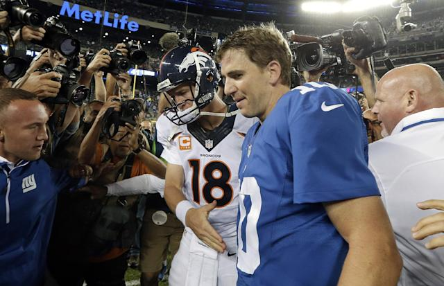 Denver Broncos quarterback Peyton Manning (18) shakes hands with his brother New York Giants' quarterback Eli Manning (10) after an NFL football game Sunday, Sept. 15, 2013, in East Rutherford, N.J. The Broncos won the game 41-23. (AP Photo/Frank Franklin II)