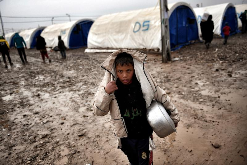 A displaced Iraqi boy from Mosul walks under the rain at the Hamam al-Alil camp on March 13, 2017