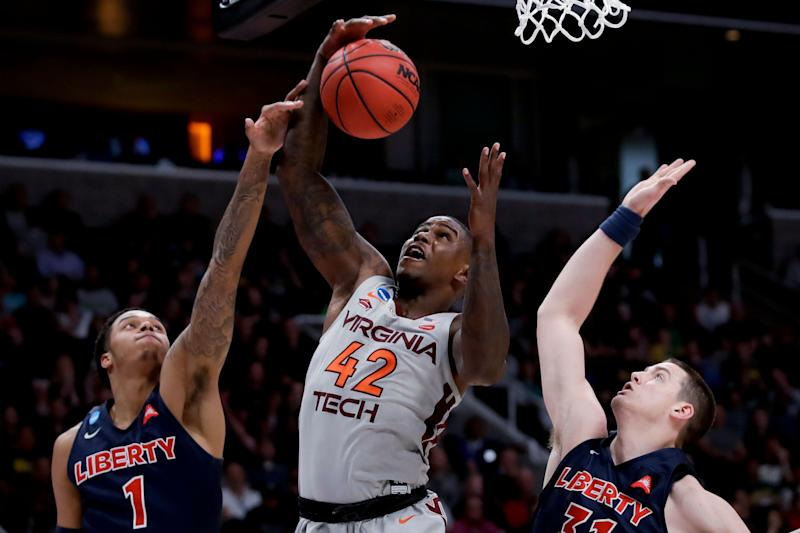 Virginia Tech guard Ty Outlaw, middle, vies for a rebound with Liberty guard Caleb Homesley, left, and Scottie James during the second half of a second-round game in the NCAA men's college basketball tournament Sunday, March 24, 2019, in San Jose, Calif. (AP Photo/Ben Margot)
