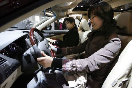 Visitors check the features of a Lexus car at the Beijing International Automotive Exhibition in this November 22, 2006 file photo. REUTERS/Claro Cortes IV