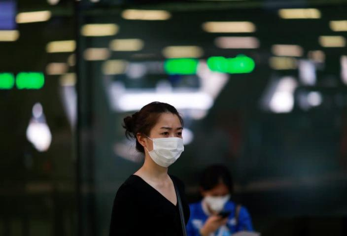 A tourist wears a mask to prevent the spread of the new coronavirus as she arrives at the Suvarnabhumi Airport in Bangkok