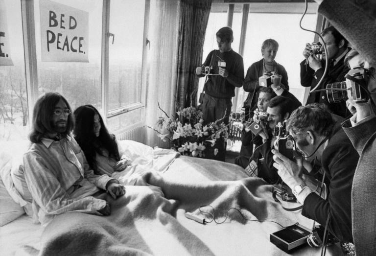 """John Lennon, pictured during his 1969 """"bed in"""" with Yoko Ono, was very short-sighted but didn't wear glasses in public in his early Beatles days"""