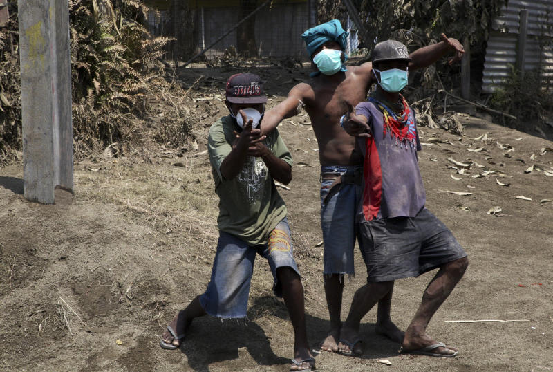 Youths wearing masks plays among ash spewed after the eruption of Mount Tavurvur in eastern Papua New Guinea on August 30, 2014 (AFP Photo/Ness Kerton)