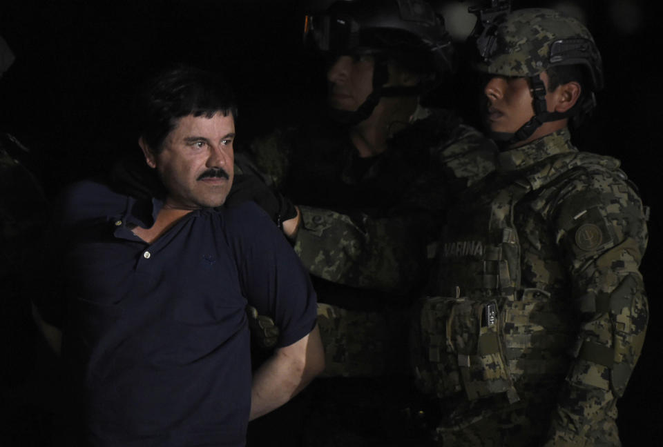 """Drug kingpin Joaquin """"El Chapo"""" Guzman is escorted to a helicopter at Mexico City's airport on January 8, 2016 following his recapture during an intense military operation in Los Mochis, in Sinaloa State. Mexican marines recaptured fugitive drug kingpin Joaquin """"El Chapo"""" Guzman on Friday in the northwest of the country, six months after his spectacular prison break embarrassed authorities.   AFP PHOTO / ALFREDO ESTRELLA / AFP / ALFREDO ESTRELLA        (Photo credit should read ALFREDO ESTRELLA/AFP/Getty Images)"""