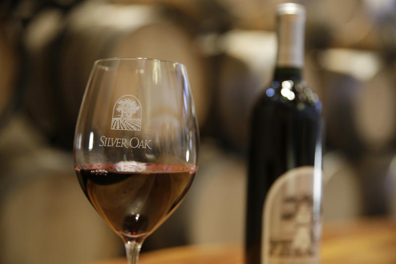This Tuesday, March 3, 2015 photo shows a glass of Cabernet Sauvignon wine in front of American Oak barrels on display at Silver Oak Cellars in Oakville, Calif. (AP Photo/Eric Risberg)