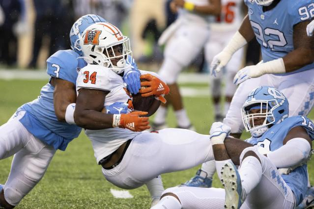 Mercer's Tyray Devezin (34) is tackled by North Carolina's Dominique Ross (3) and Tomon Fox (12) during the first half of an NCAA college football game in Chapel Hill, N.C., Saturday, Nov. 23, 2019. (AP Photo/Ben McKeown)