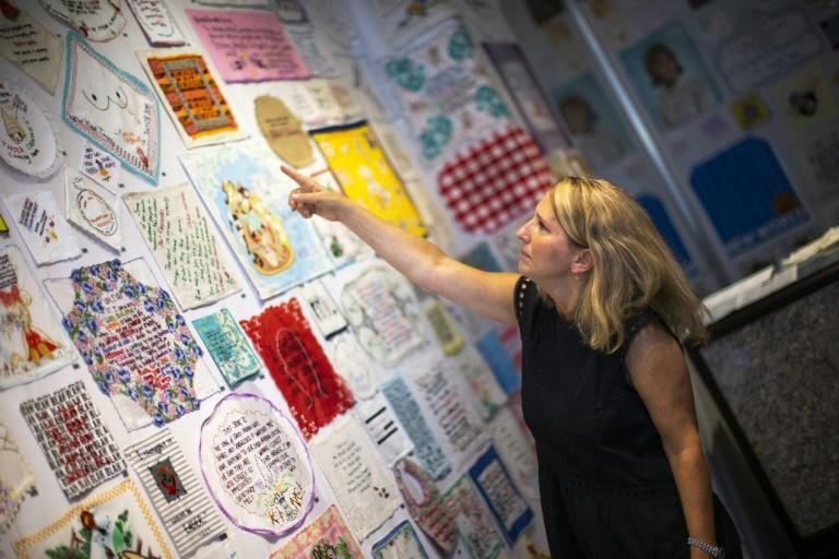 "Textile artist Diana Weymar points to some of her ""Tiny Pricks"" project pieces at Lingua Franca store during a interview with AFP, on July 25, 2019 in New York City"