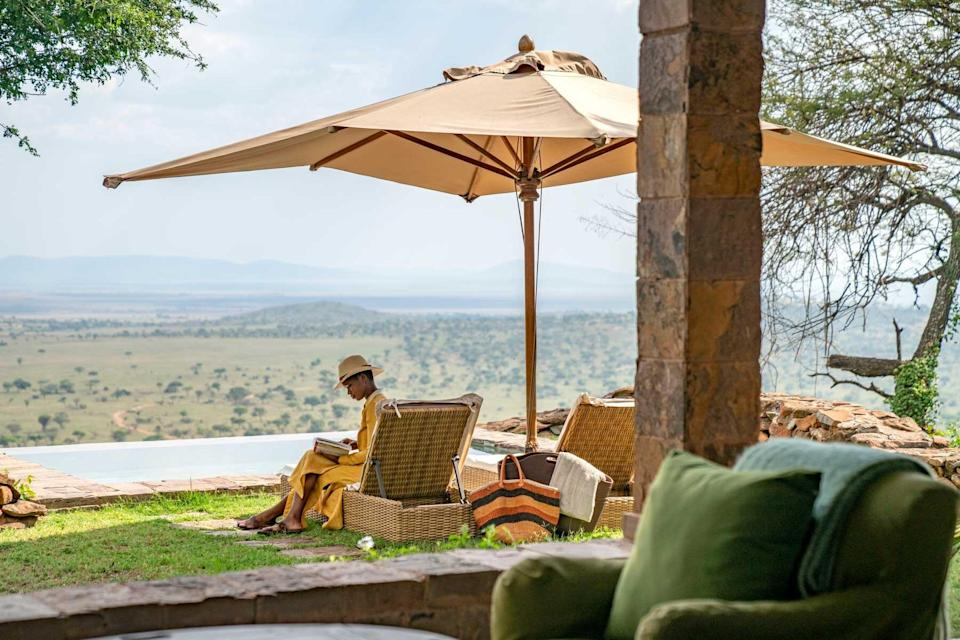 A woman reads on the terrace at Singita Grumeti, voted one of the best hotels in the world