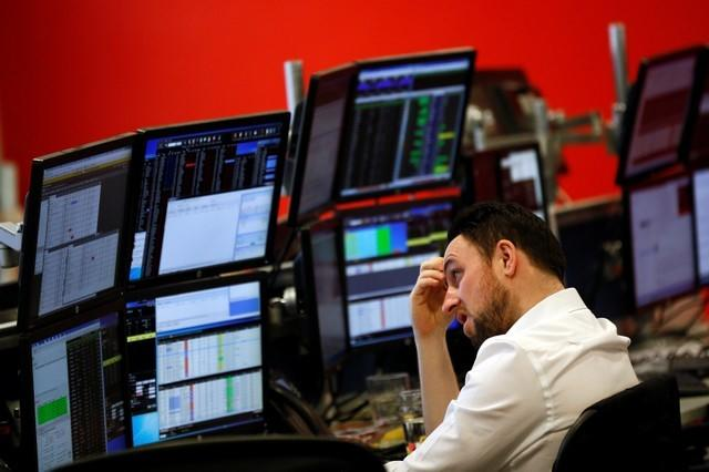 FILE PHOTO: A market maker works on the trading floor at IG Index in London