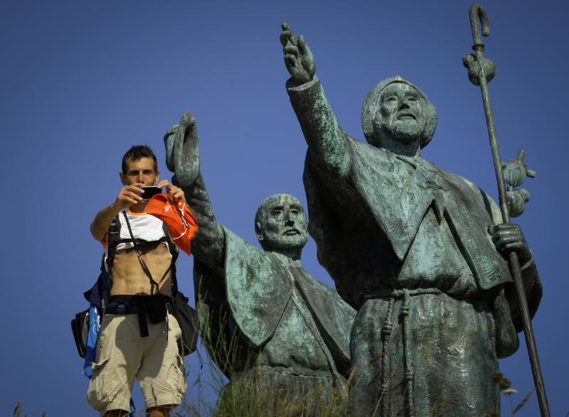 A pilgrim takes a 'selfie' on the Way of Saint James, at the Gozo Mount, close to Santiago de Compostela, on August 21, 2014