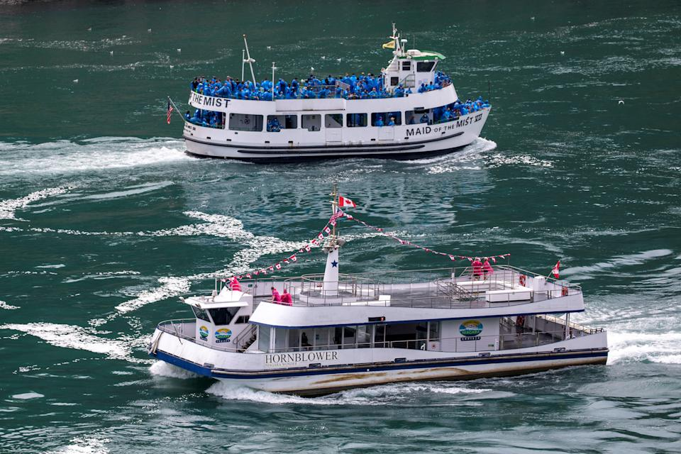 American tourist boat Maid Of The Mist, limited to 50 per cent occupancy glides past a Canadian vessel limited under Ontario's rules to just six passengers. Source: Reuters