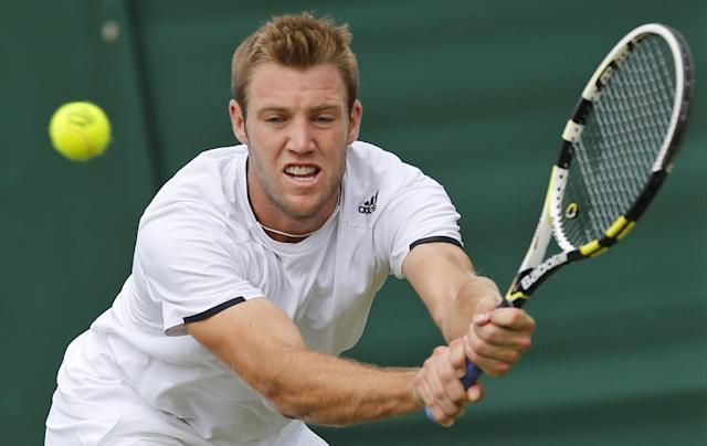 Jack Sock of the U.S. returns to Milos Raonic of Canada during their men's singles match at the All England Lawn Tennis Championships in Wimbledon, London, Thursday, June 26, 2014. (AP Photo/Ben Curtis)