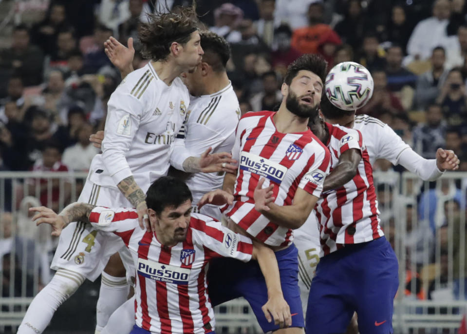 Atletico Madrid's players and Real Madrid's players jump for the ball during the Spanish Super Cup Final soccer match between Real Madrid and Atletico Madrid at King Abdullah stadium in Jiddah, Saudi Arabia, Sunday, Jan. 12, 2020. (AP Photo/Hassan Ammar)