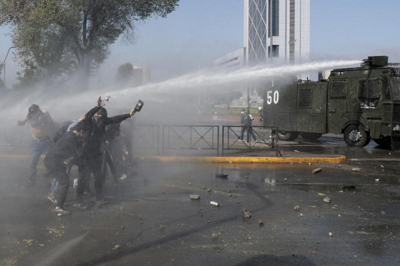 Police spray water at demonstrators blocking an avenue in Santiago, Chile, Sunday, Oct. 20, 2019. Protests in the country have spilled over into a new day, even after President Sebastian Pinera cancelled the subway fare hike that prompted massive and violent demonstrations. (Photo: Esteban Felix/AP)