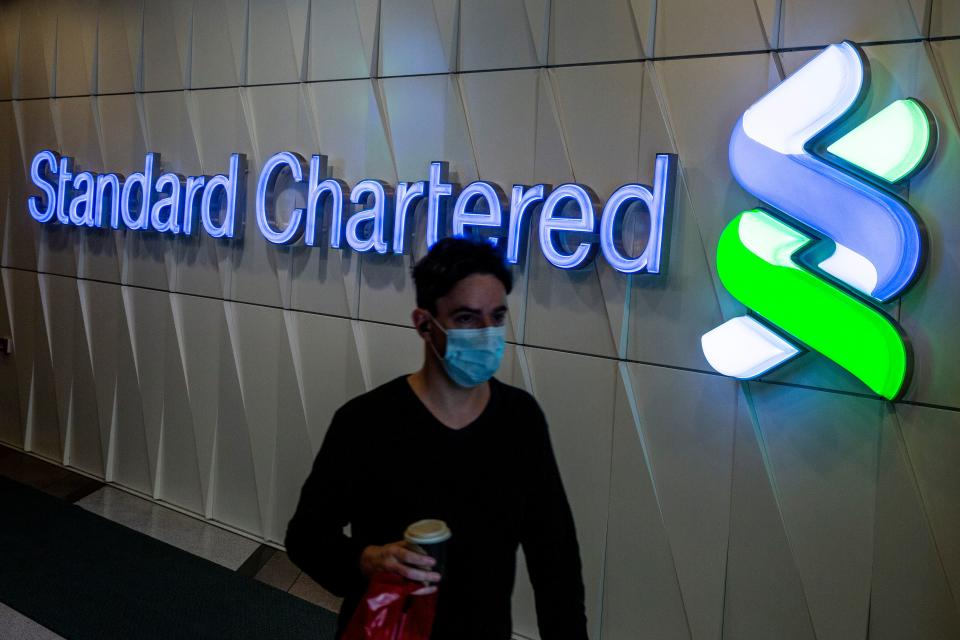 A man walks past a Standard Chartered sign in Hong Kong on February 27, 2020. - Standard Chartered said that its pre-tax profit rose to 4.2 billion USD in 2019, but warned that the income growth will be lower than target in 2020 over coronavirus woes. (Photo by ISAAC LAWRENCE / AFP) (Photo by ISAAC LAWRENCE/AFP via Getty Images)