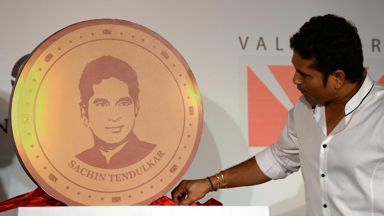 Indian cricketer Sachin Tendulkar looks at large model of a limited edition 10 gram gold coin with an embossed image of himself after unveiling it on Akshaya Tritiya in Mumbai on May 13, 2013. A total of 100, 000 limited edition 10 gram Tendulkar Gold coins priced at INR 34,000 (USD 618) will be available for both online purchase and at retail stores of leading jewellers across the country. Akshaya Tritiya is considered to be an auspicious day in the Hindu calendar to buy valuables and people generally flock to buy gold on this day in the belief that it will increase their wealth.   AFP PHOTO/ Indranil MUKHERJEE