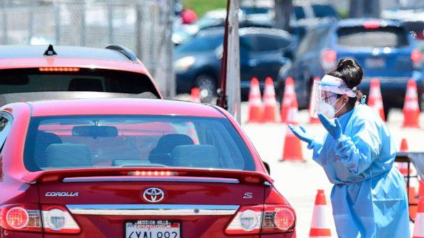 PHOTO: A volunteer dressed in personal protective equipment gestures to a driver in line at a COVID-19 testing site in the Panoramic City neighborhood of Los Angeles, California, on July 30, 2020. (Frederic J. Brown/AFP via Getty Images)