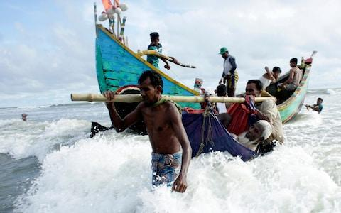 Rohingya refugees carry an old man towards the shore of Naf river as people arrive by boats, in Teknaf, Bangladesh - Credit: EPA