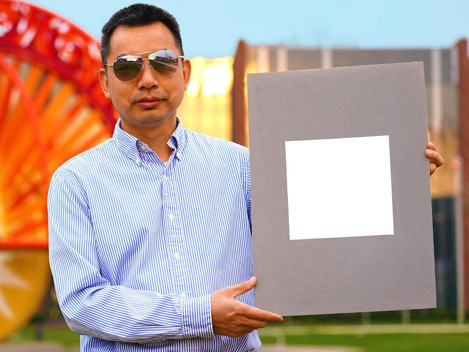 Developer Xiulin Ruan holds up a sample of the 'whitest paint'  (Purdue University/Jared Pike)