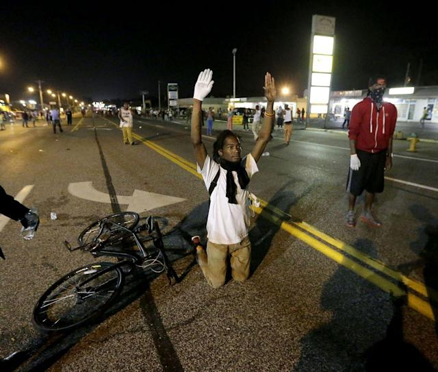 <p>A man holds his hands up in the street after a standoff with police Monday, Aug. 18, 2014, during a protest for Michael Brown, who was killed by a police officer Aug. 9 in Ferguson, Mo. (Charlie Riedel/AP) </p>