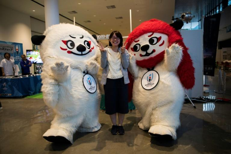 A Japanese woman poses with Rugby World Cup 2019 mascots, Ren (L) and G (R) at a rugby pop-up museum in Kamaishi