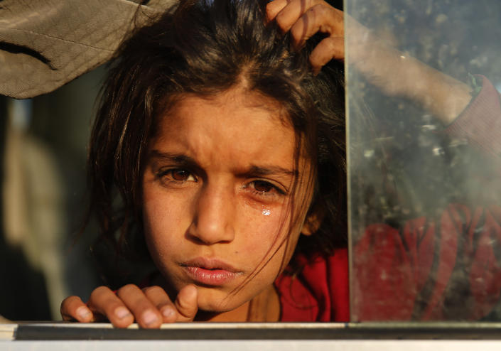 A Syrian girl who is newly displaced by the Turkish military operation in northeastern Syria, weeps as she sits in a bus upon her arrival at the Bardarash camp, north of Mosul, Iraq, Oct. 16, 2019. (Photo: Hussein Malla/AP)