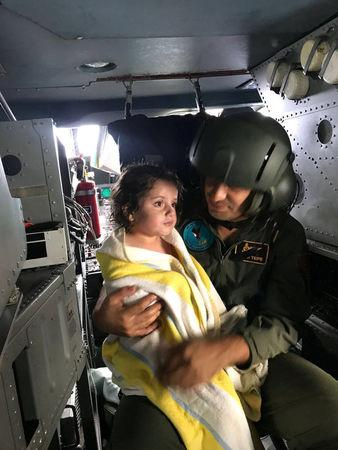 A Turkish military personnel holds a girl in a helicopter after she survied from a sunken migrant boat, in Kandira, Turkey, September 22, 2017. Turkish Military/Handout via REUTERS
