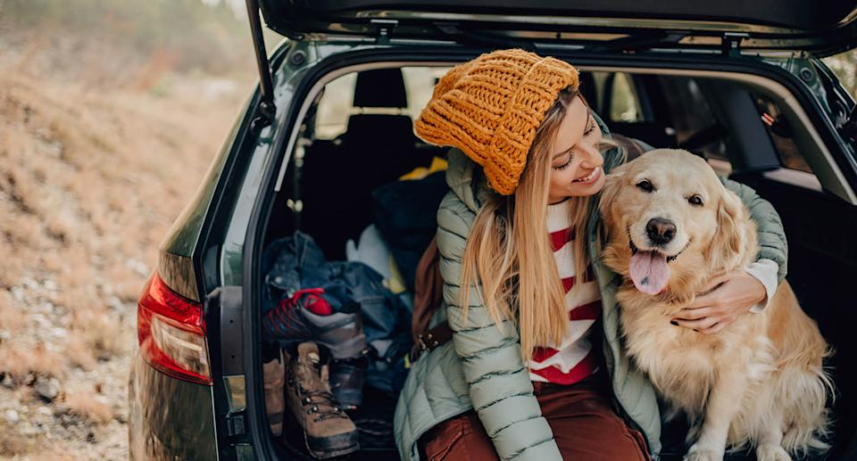 Woman and dog sit in open boot. Source: Getty Images