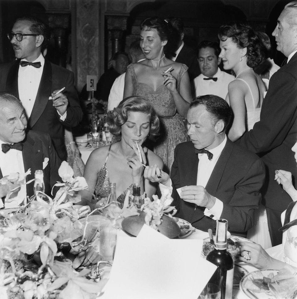 <p>Frank Sinatra lights a cigarette for actress Lauren Bacall at a premiere party for <em>A Star is Born </em>in 1954. The couple had a brief romance after the death of Bacall's husband, Humphrey Bogart.</p>