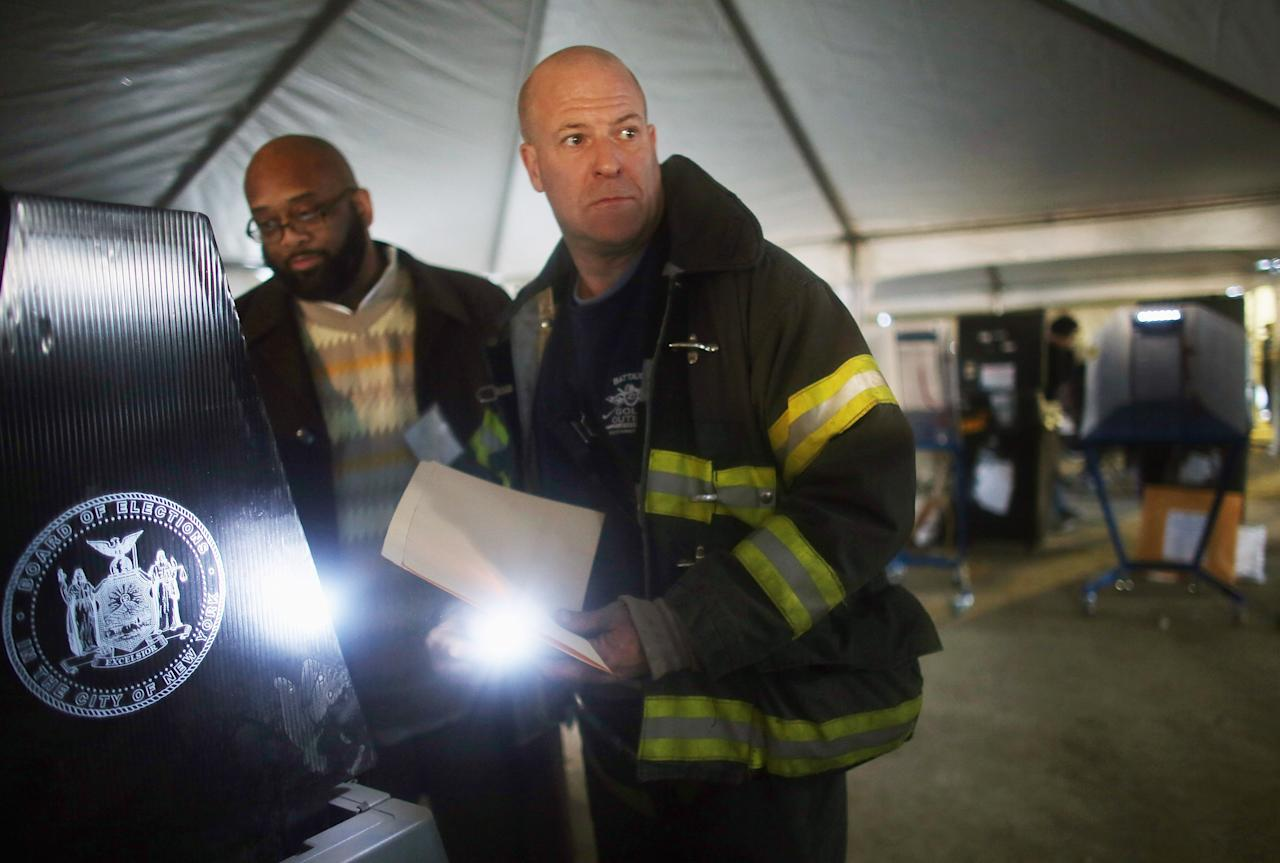 Rockaway resident and New York City firefighter Terence O'Donnell holds a flashlight while voting in a makeshift tent set up as a polling place at Scholars' Academy, PS 180, in the Rockaway neighborhood on November 6, 2012 in the Queens borough of New York City. The Rockaway section of Queens was one of the hardest hit areas and O'Donnell's home is damaged. Many voters in New York and New Jersey are voting at alternate locations in the presidential election due to disruption from Superstorm Sandy.    (Photo by Mario Tama/Getty Images)