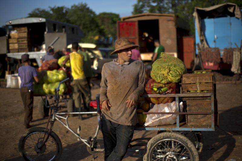 A vendor leans against his bike with cart stacked with vegetables he purchased at a food market, to resell on the streets, on the outskirts in Havana, Cuba, Wednesday, Sept. 25, 2013. Cuban authorities on Thursday announced 18 new categories of independent employment that will be permitted under President Raul Castro's economic reforms, and also restrictions intended to regulate other private entrepreneurs already in business. (AP Photo/Ramon Espinosa)
