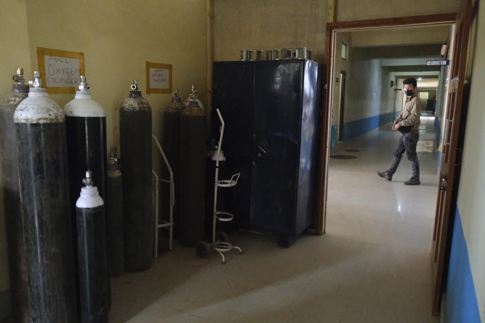 A man walks past a room where oxygen cylinders are stored at the District Hospital in Ukhrul, in the northeastern Indian state of Manipur, Friday, Jan. 15, 2021. This is the only government-run medical facility in the district that caters to a population of 180,000. The country's COVID-19 vaccination campaign that began Saturday is also being carried out here. (AP Photo/Yirmiyan Arthur)
