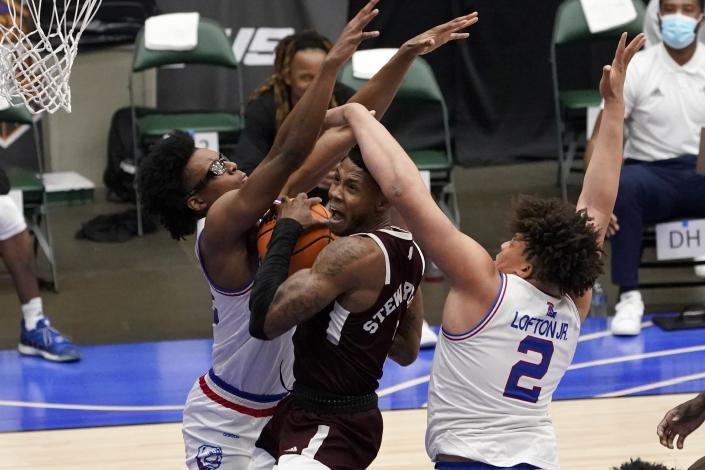 Louisiana Tech forward Isaiah Crawford, left, and forward Kenneth Lofton Jr., (2) defend as Mississippi State guard D.J. Stewart Jr., center, leaps to the basket for a shot in the first half of an NCAA college basketball game in the semifinals of the NIT, Saturday, March 27, 2021, in Frisco, Texas. (AP Photo/Tony Gutierrez)