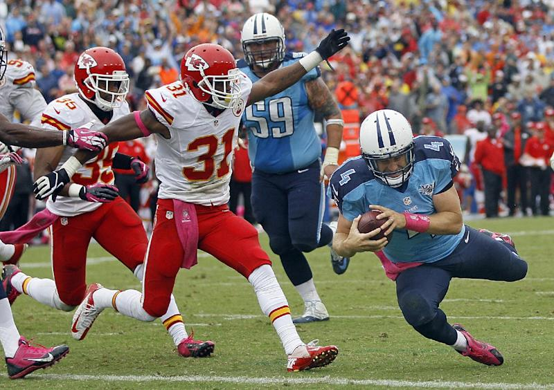 Tennessee Titans quarterback Ryan Fitzpatrick (4) dives into the end zone to score a touchdown on a 9-yard run against the Kansas City Chiefs in the fourth quarter of an NFL football game on Sunday, Oct. 6, 2013, in Nashville, Tenn. Chiefs' Marcus Cooper (31) and Quintin Demps (35) defend on the play. (AP Photo/Wade Payne)