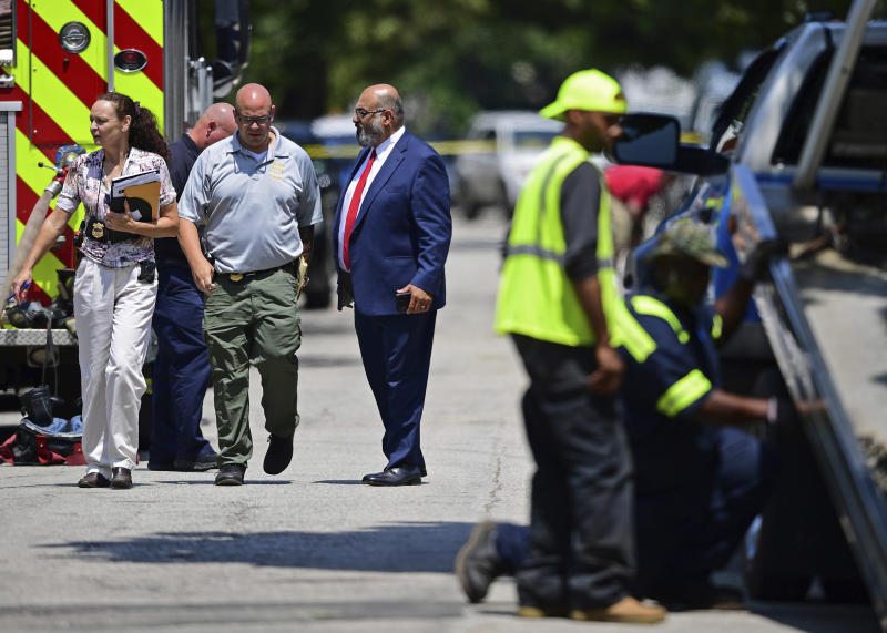 Police officers walk to the crime scene, Tuesday, July 9, 2019, in Cleveland. Police investigating the shooting death of a man in a vacant lot say they also found the bodies of a woman and two children in a nearby house. Authorities aren't saying how the three found inside the house Tuesday died, but they did say the four deaths are connected. (AP Photo/David Dermer)