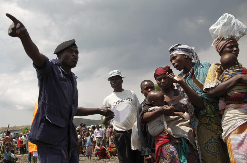 A Congolese national police officer directs internally displaced Congolese women waiting for food to be distributed by WFP at the Mugunga 3 camp outside the eastern Congolese town of Goma, Sunday Dec. 2, 2012. Rebels say they will take back Congo's city of Goma if the government does not agree to negotiate with them by Monday. The M23 rebels completed their withdrawal of the eastern Congo city on Saturday, in compliance with an agreement reached between the rebel group and a regional body. (AP Photo/Jerome Delay)