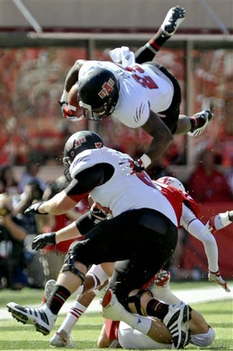 Arkansas State's David Oku, top, leaps over Alan Wright and Nebraska's Braylon Heard and Joey Felici, rear, in the first half of their NCAA college football game in Lincoln, Neb., Saturday, Sept. 15, 2012. (AP Photo/Dave Weaver)