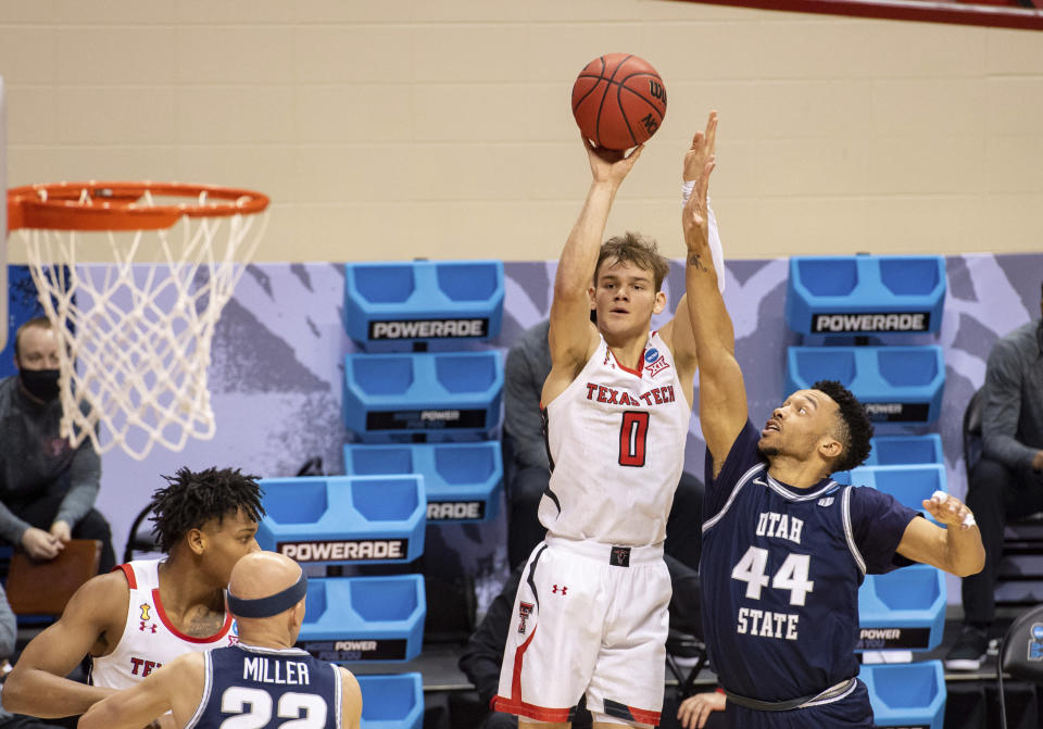 Texas Tech guard Mac McClung (0) shoots a 3-point shot while Utah State guard Marco Anthony (44) defends during the second half of a first round game in the NCAA men's college basketball tournament, Friday, March 19, 2021, at Assembly Hall in Bloomington, Ind. (AP Photo/Doug McSchooler)