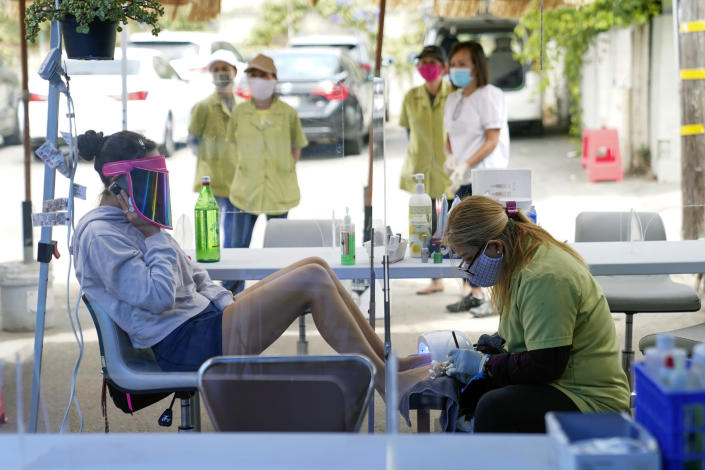"FILE - In this July 22, 2020, file photo, Tyson Salomon, left, gets a pedicure outside Pampered Hands nail salon in Los Angeles. A steady drop in coronavirus cases across California cleared the way Tuesday, Sept. 22, 2020, for the wider reopening of businesses in nine counties, including much of the San Francisco Bay Area, the state's top health official said. Dr. Mark Ghaly, the state health secretary, said nail salons could also reopen with restrictions, though he cautioned that California's reopening must remain ""slow and stringent"" and residents cannot let their guard down as flu season arrives and cases rise in Europe and other parts of the U.S. (AP Photo/Ashley Landis, File)"