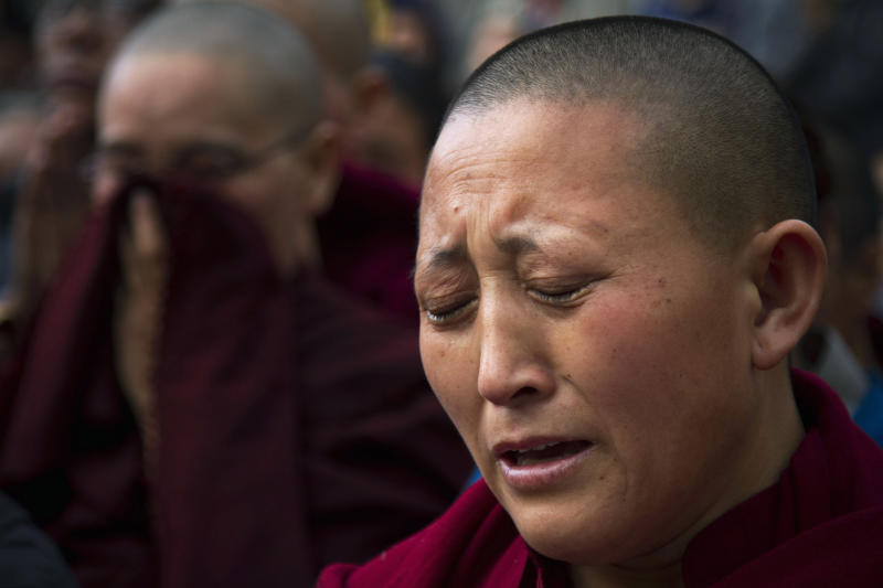 An exile Tibetan Buddhist nun cries in Dharmsala, India, Monday, March 26, 2012 during a candle lit vigil in solidarity with a 27-year-old Tibetan Jamphel Yeshi, who immolated himself in New Delhi, just ahead of a visit by China's president Hu Jintao. (AP Photo/Ashwini Bhatia)