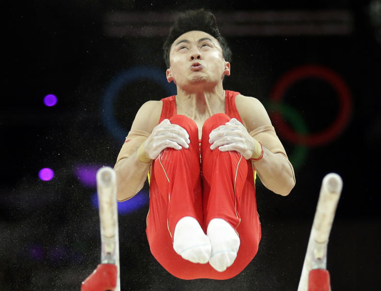 Chinese gymnast Feng Zhe performs on the parallel bars during the Artistic Gymnastic men's qualification at the 2012 Summer Olympics, Saturday, July 28, 2012, in London. (AP Photo/Gregory Bull)